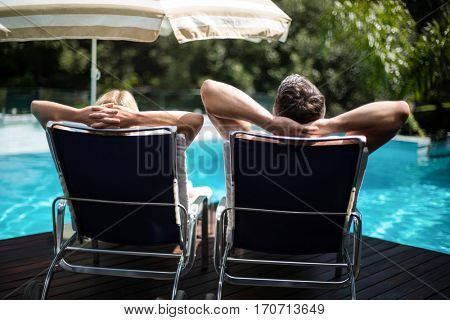 Rear view of couple relaxing on sun lounger near pool
