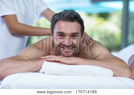 Portrait of man receiving back massage from masseur in spa