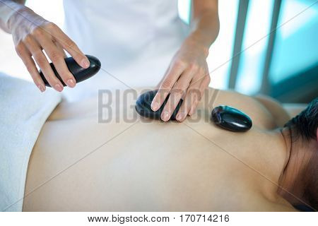 Mid section of man receiving a hot stone massage from masseur