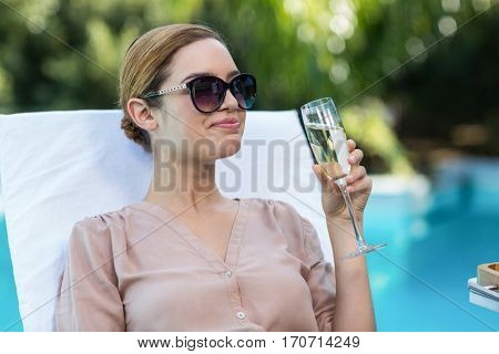 Business woman drinking champagne and relaxing on sun lounger near pool