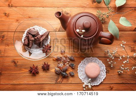 Teapot and sweets on wooden table
