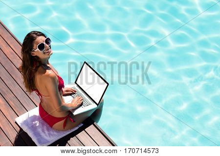 Woman using her laptop on the pool edge on a sunny day