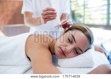 Woman receiving ear candle treatment at spa