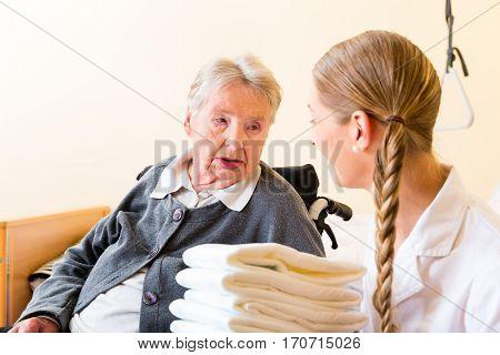 Nurse bringing supplies to senior woman in retirement home
