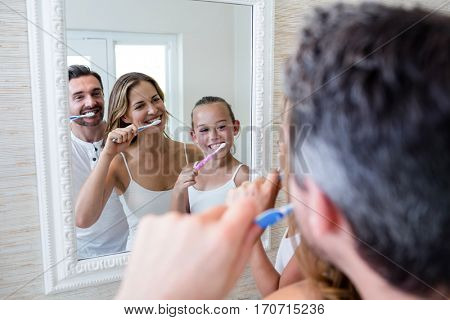 Parents and daughter brushing their teeth in the bathroom at home