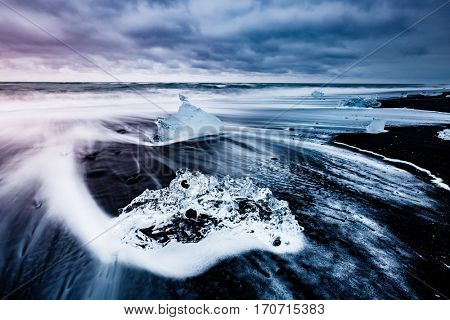 Large pieces of the iceberg that sparkle on the black sand. Picturesque and gorgeous scene. Location famous place Jokulsarlon lagoon, Vatnajokull national park, south Iceland, Europe. Beauty world.