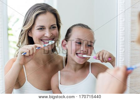Mother and daughter brushing their teeth in the bathroom