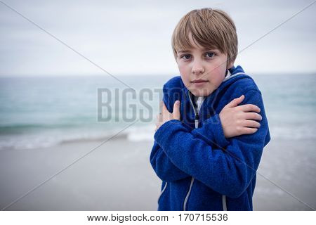 Portrait of boy in blue jacket feeling cold at beach