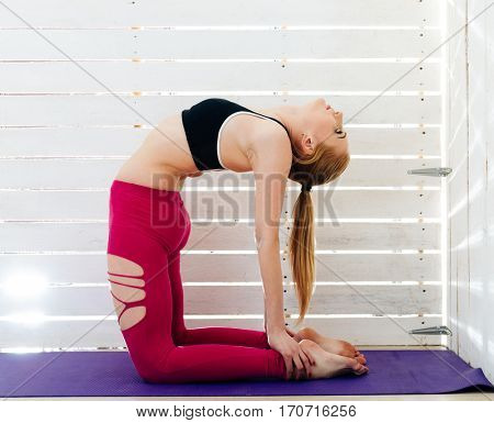 Woman practicing yoga. Yogi against the light from the window. Exercises for strength and stretching.