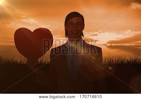 Geeky businessman smiling and holding heart card against a couldy day