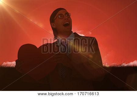 Geeky businessman smiling and holding heart card against red sky over grass