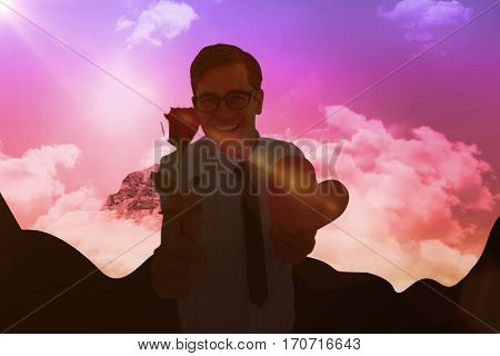 Geeky hipster holding a red rose and heart card against sky and mountain