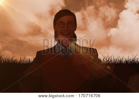 Geeky businessman smiling and holding heart card against cloud filled sky