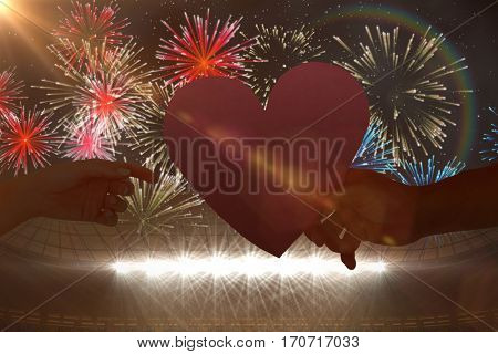 Couple passing a paper heart against fireworks exploding over football stadium