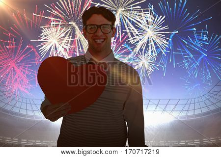 Geeky hipster holding heart card against fireworks exploding over football stadium