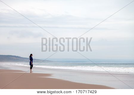 Lonely and depressed woman watching the sea in a deserted beach on an Autumn day.