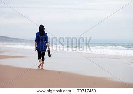 Young woman walking away alone in a deserted beach on an Autumn day.