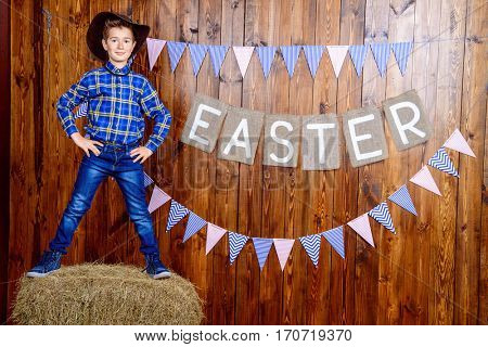 Portrait of a cute nine year old boy posing in Easter decorations. Western style, cowboy. Kid's fashion. Easter.