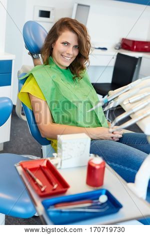 Smiling female patient sitting in dentist's chair.