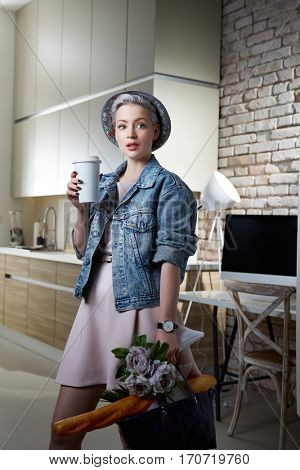 Young woman arriving at home with shopping bag and coffee.