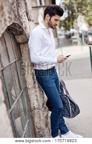 Casual young man writing text message on mobilephone outdoors.