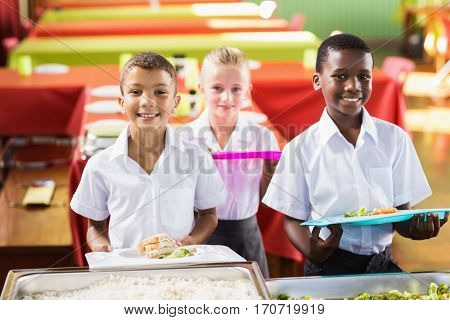 Portrait of student holding food tray in school cafeteria