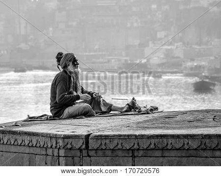 old man seeing time going by in a platform above the Gange river