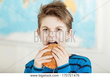 Young Vegetarian Biting Into A Carrot Burger