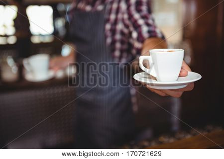 Waiter handing over a coffee in a restaurant
