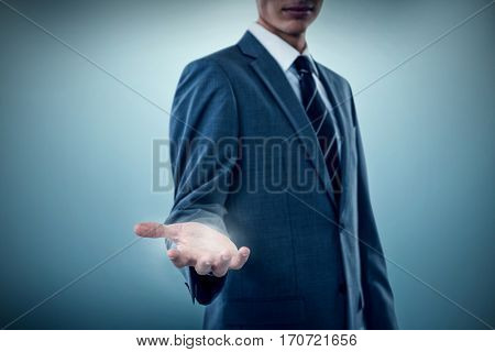 Midsection of sophisticated businessman offering against grey vignette