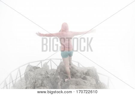 young woman climbing a mountain on the peak