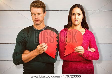 Portrait of serious couple holding cracked heart shape against painted blue wooden planks