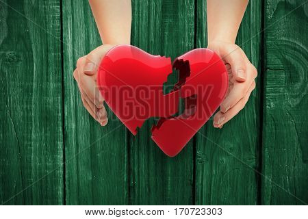 Hands presenting against green wooden background