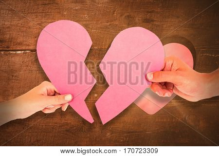 Couple holding two halves of broken heart against heart in wood