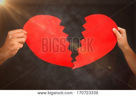 Cropped couple hands holding red cracked heart shape against grey