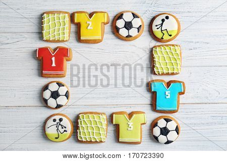 Delicious gingerbread cookies decorated with football signs on white wooden background