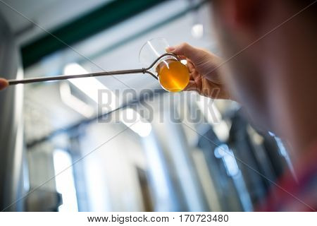 Close-up of brewer testing beer at brewery factory