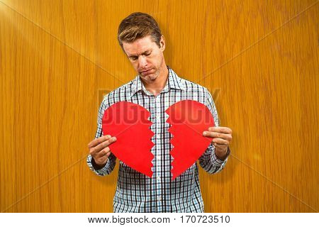 Sad man holding a broken card against wooden pine table