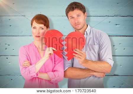 Couple holding a broken heart against painted blue wooden planks