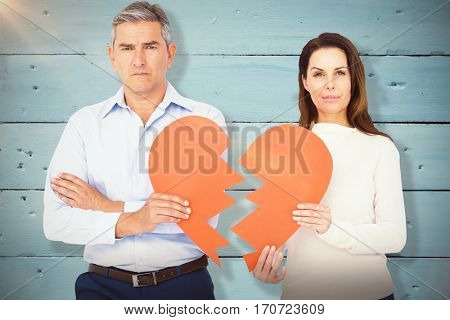 Portrait of couple holding broken heart shape paper against painted blue wooden planks