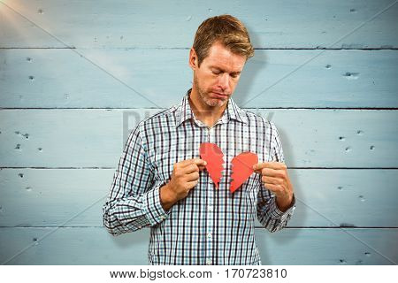 Sad man with broken heart against painted blue wooden planks
