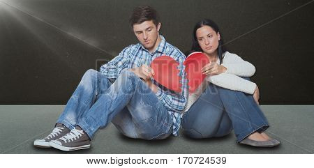 Young couple sitting on floor with broken heart against dark room
