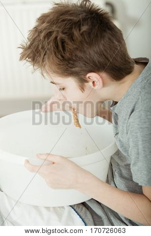 Unwell Young Boy Throwing Up Into A Bowl In Bed