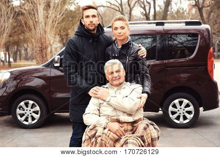Young couple with man in a wheelchair in front of his car