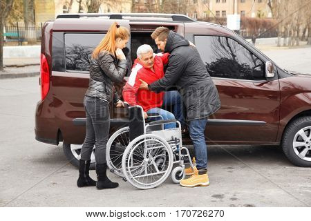 Young couple helping handicapped man to sit in wheelchair