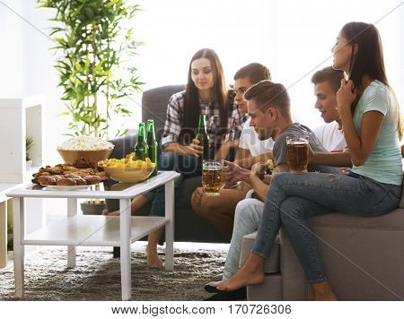 Young fans watching sports on TV with beer and snacks