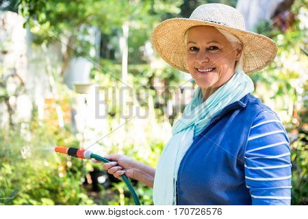 Portrait of happy mature female gardener watering from hose at garden