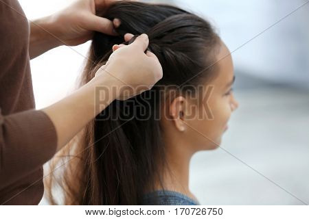 Woman doing hair of her daughter at home, closeup