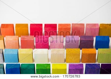 Wood blocks in different colors aligned and standing, on white background.
