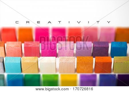 Cover for creative works. Spectrum of multi colored wooden blocks with white area with